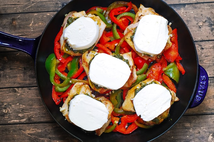 thickly sliced fresh mozzarella cheese on top of chicken thighs in a cast iron skillet