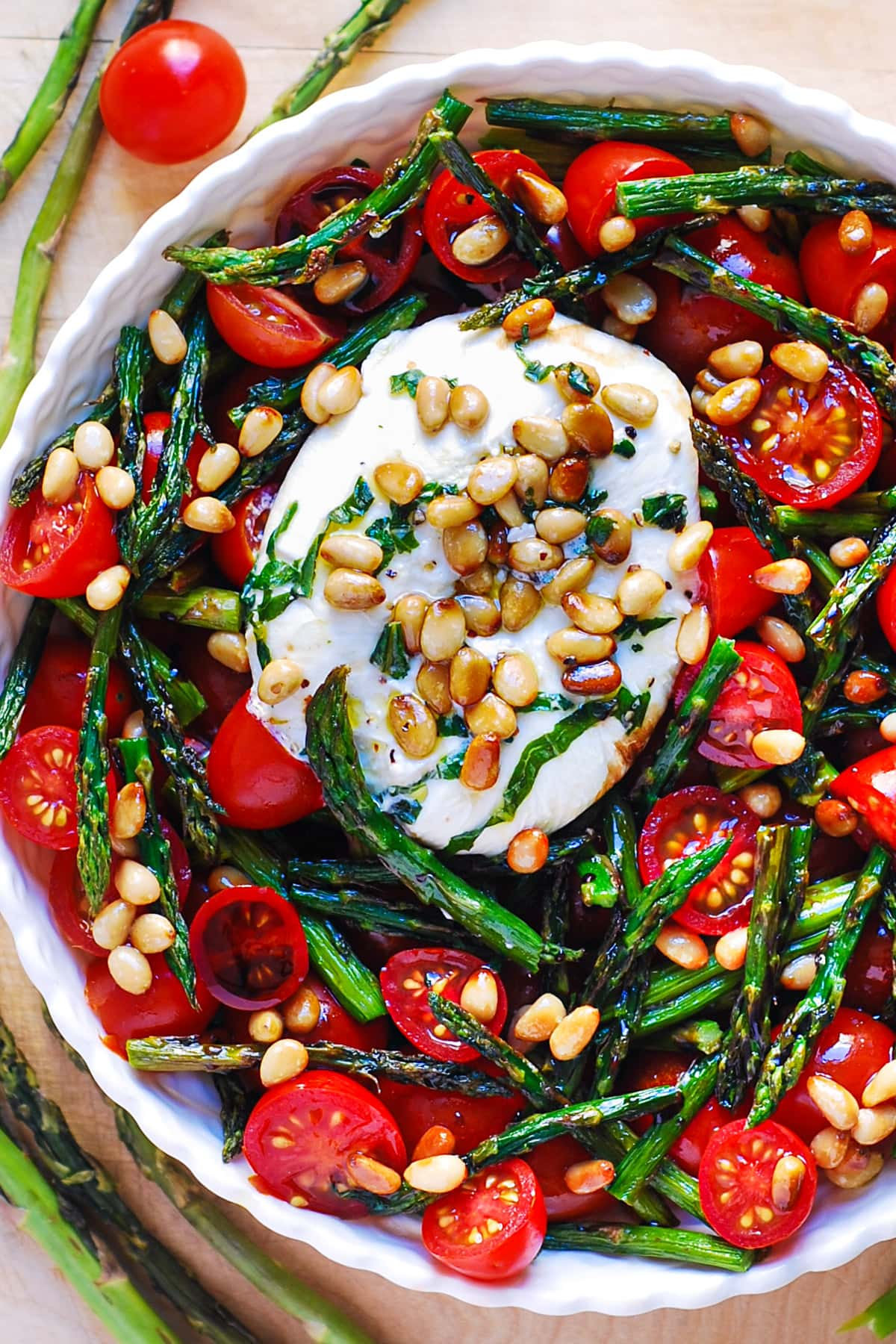 asparagus tomato salad with burrata cheese and pine nuts in a bowl
