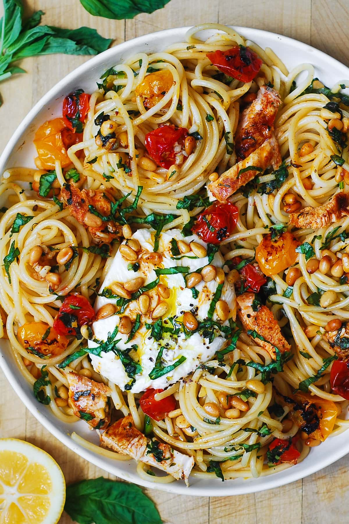 chicken spaghetti with burrata cheese, roasted cherry (or grape) tomatoes, pine nuts on a white plate