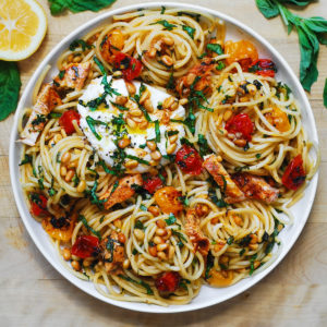 Chicken Spaghetti with Burrata, cherry tomatoes, and pine nuts on a white plate