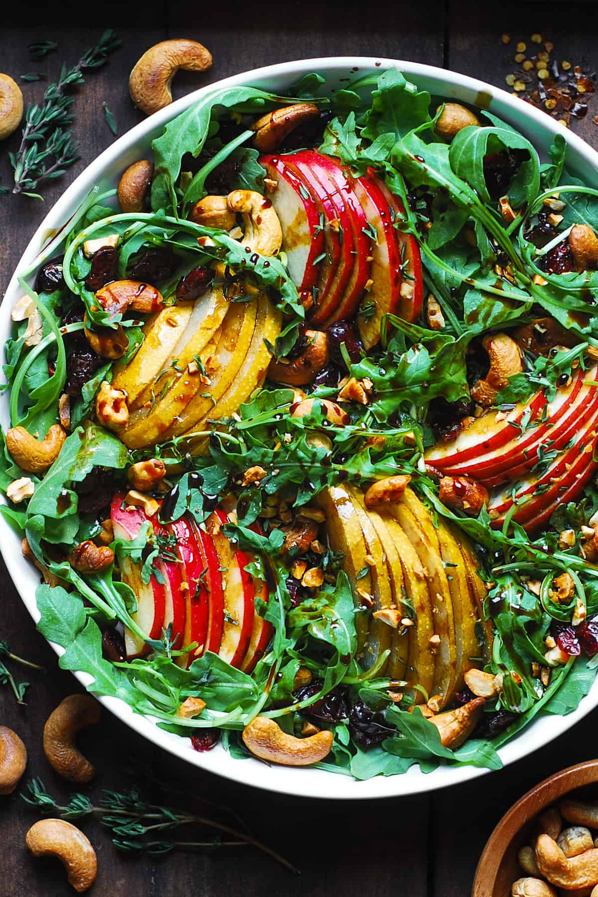 arugula salad with pears, apples, cashews, and dried cranberries in a white bowl