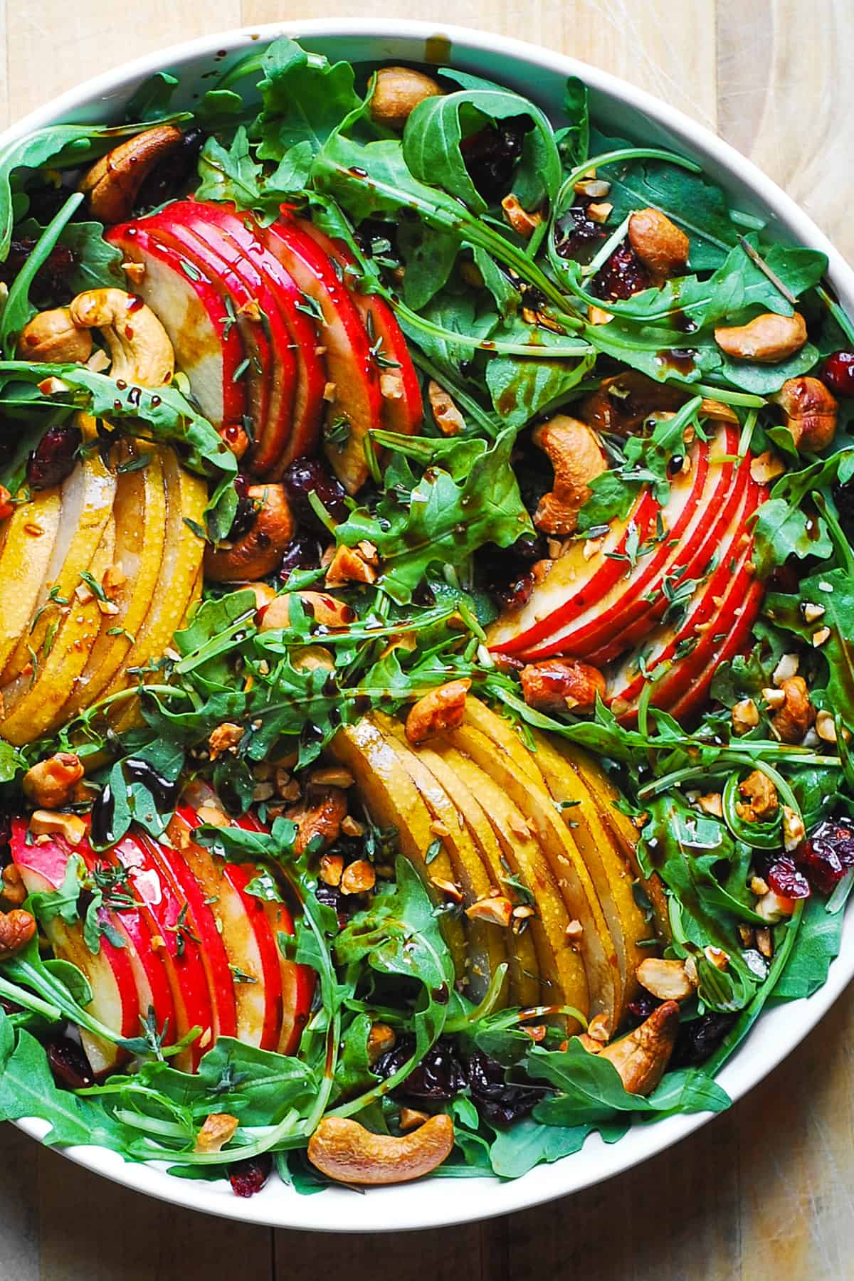 arugula salad with pears, apples, cashews, dried cranberries in a white bowl