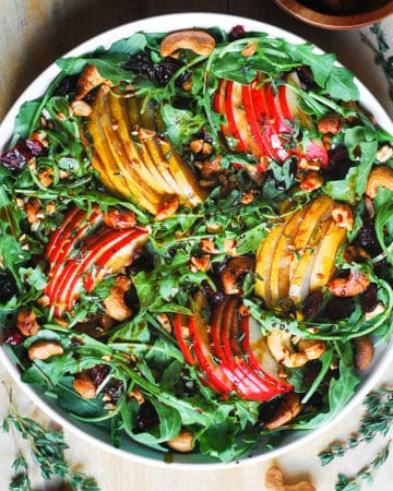arugula salad with pears, apples, dried cranberries, cashews in a white bowl