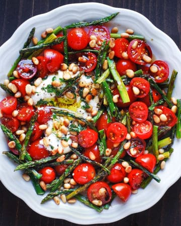 asparagus tomato salad with burrata cheese and pine nuts in a white bowl