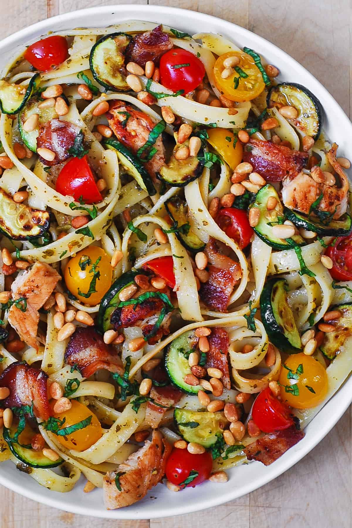 chicken bacon zucchini pasta with cherry tomatoes, basil, and pine nuts on a white pasta plate