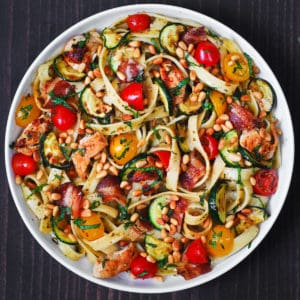 chicken bacon zucchini pasta with tomatoes and pine nuts on a white plate