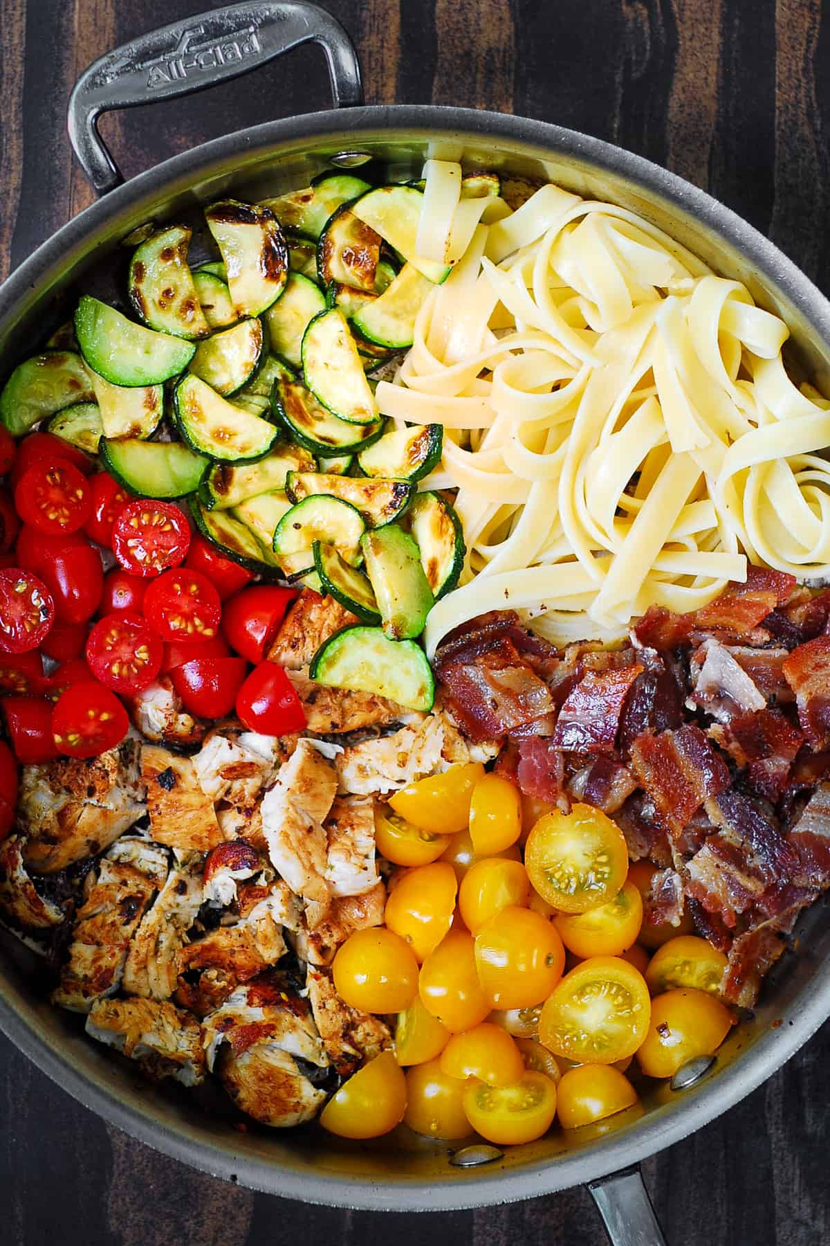 sections of food in a stainless steel pan: cooked sliced zucchini, cooked fettuccine, cooked chopped bacon, cherry tomatoes, cooked sliced chicken