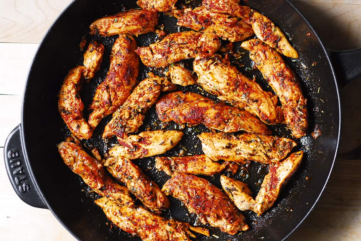cooked chicken tenderloins in a cast-iron skillet