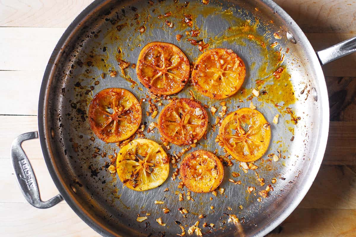 cooked lemon slices and garlic in a stainless steel pan