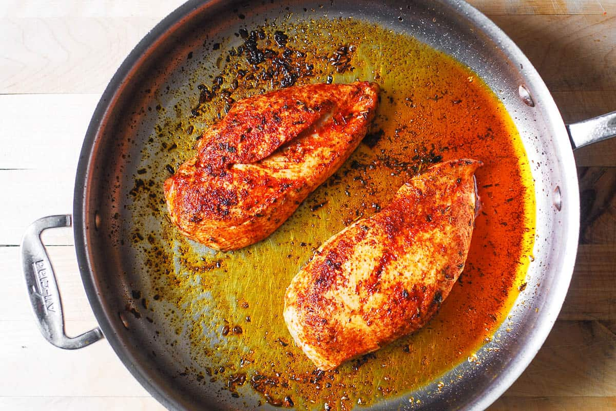 cooked chicken breasts in a stainless steel pan
