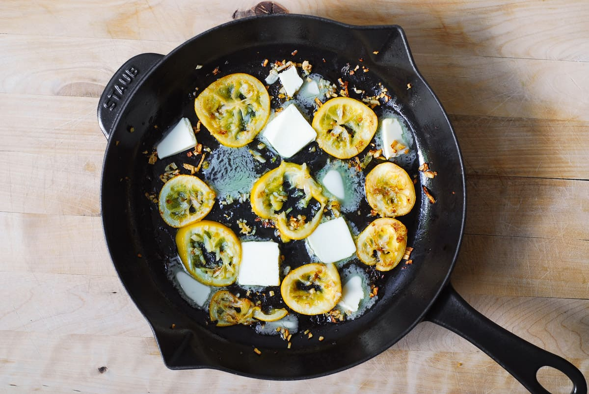butter, cooked lemon slices, minced garlic in a cast iron skillet