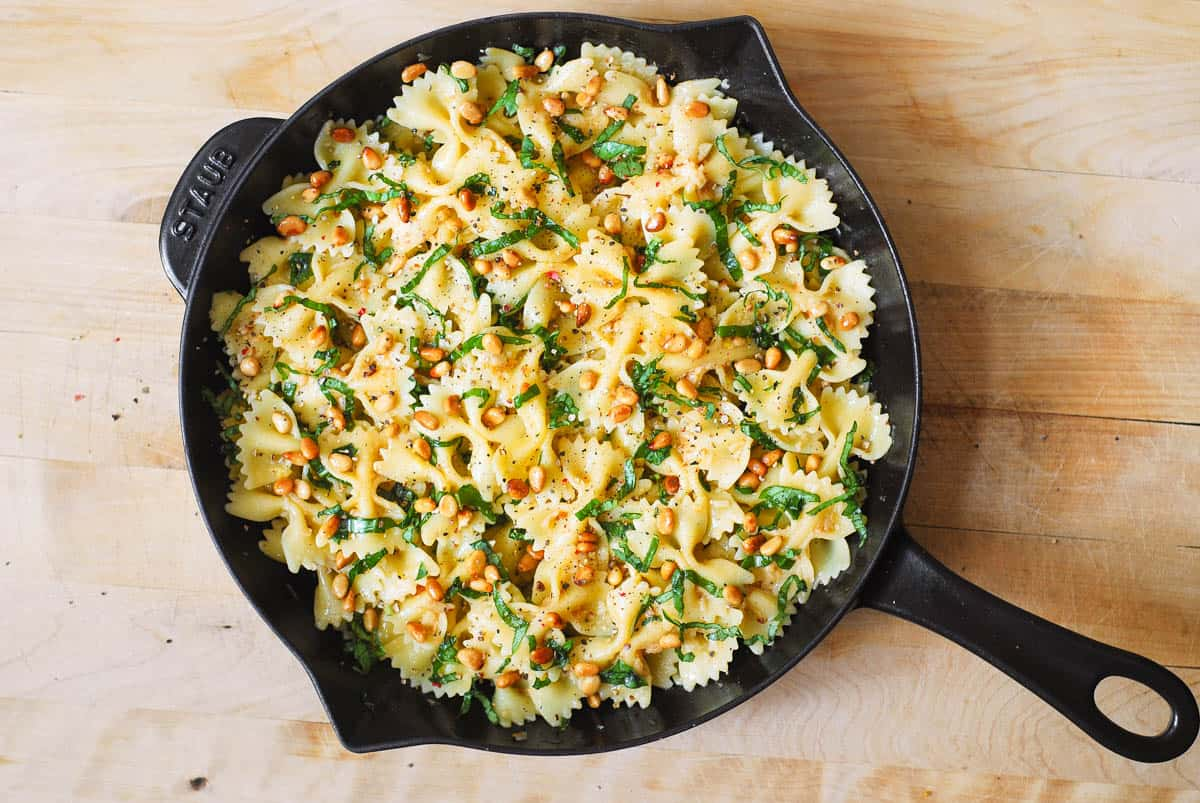 chopped fresh basil and toasted pine nuts on top of bow tie pasta in a cast iron skillet