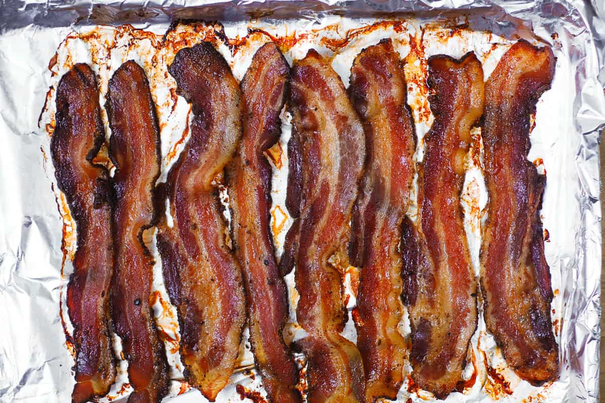 cooked bacon strips on a baking sheet