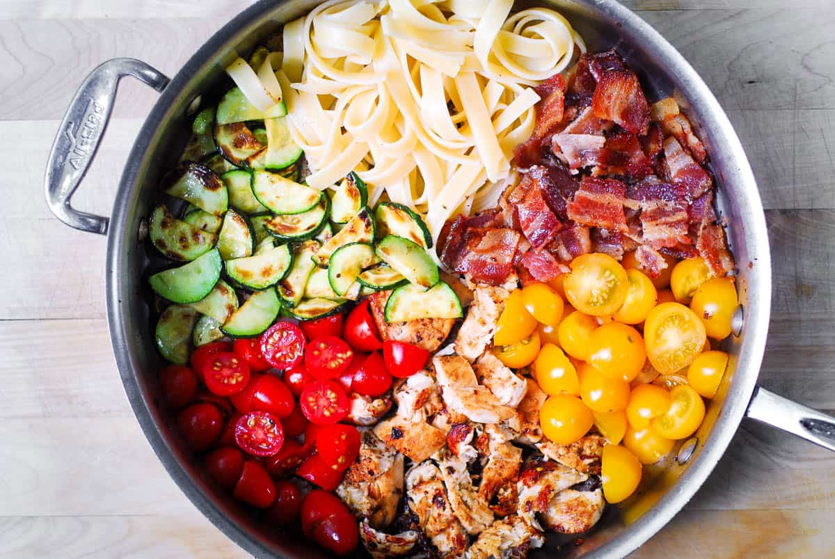 stainless steel skillet with sections of fettuccine, sliced zucchini, red and yellow grape tomatoes, cooked bacon, and cooked chicken
