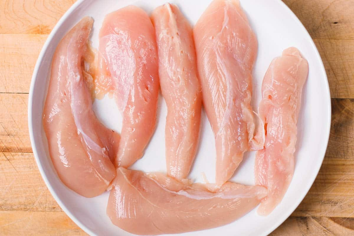 raw chicken tenders on a white plate