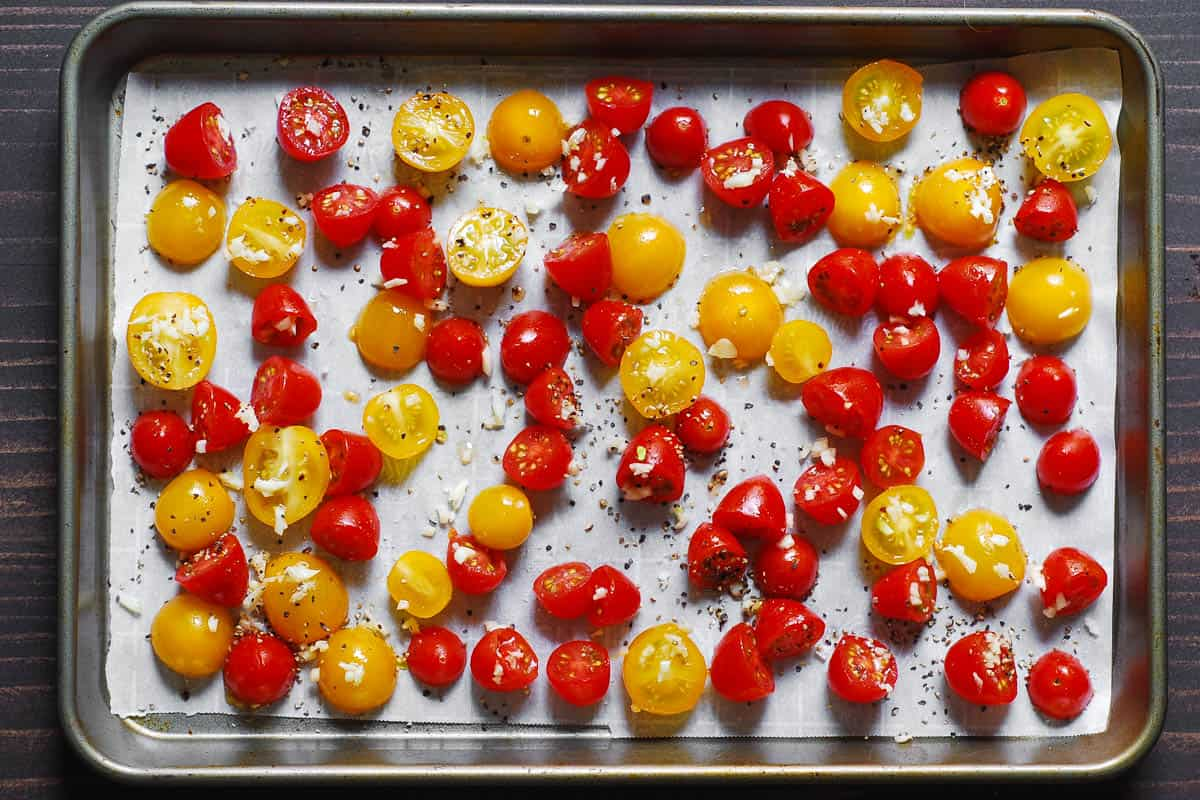 sliced cherry tomatoes with minced garlic on a baking sheet