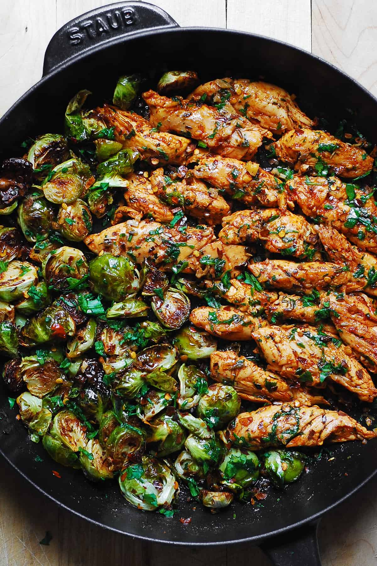 lemon garlic butter chicken and Brussels sprouts in a cast-iron skillet