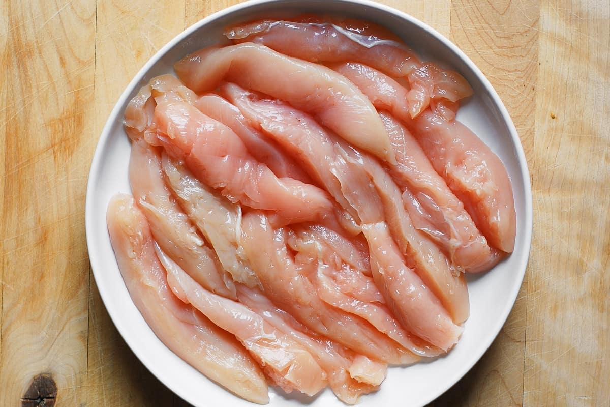 raw chicken tenderloins on a white plate