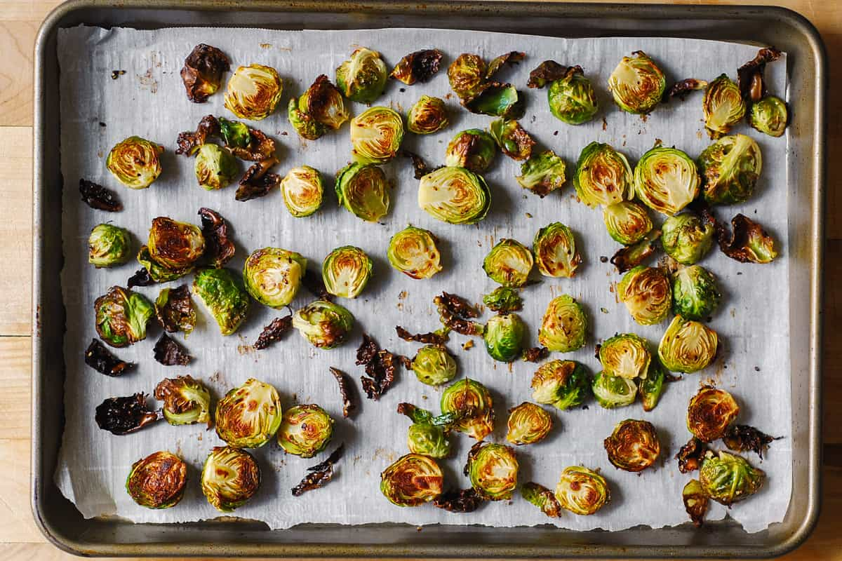 roasted Brussels sprouts on a parchment paper lined baking sheet