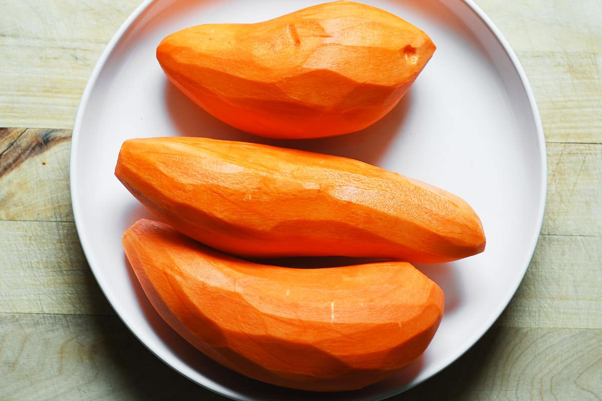 3 peeled sweet potatoes on a white plate