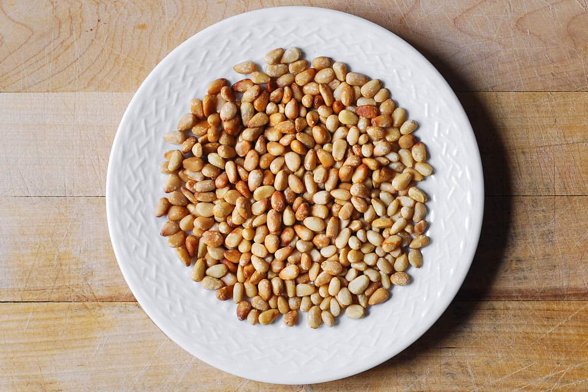 toasted pine nuts on a white plate