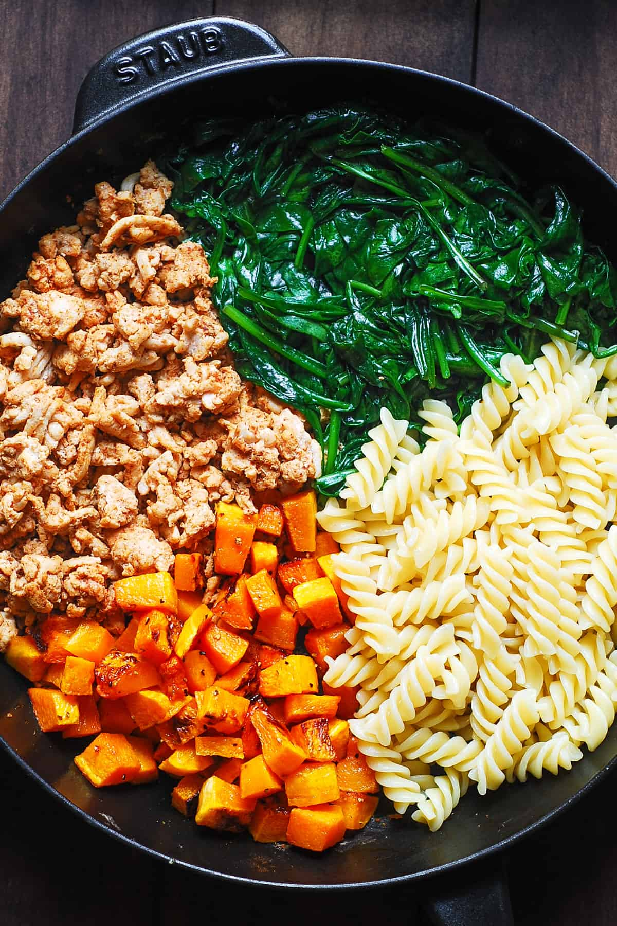 Ingredients for pasta in a cast-iron skillet: cooked ground turkey, cooked spinach, cooked pasta, roasted butternut squash