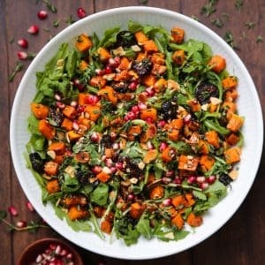Fall Salad with Butternut Squash, Arugula, Dried Figs, and Almonds in a white bowl