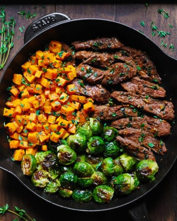 Garlic Butter Steak with Brussels Sprouts and Butternut Squash in a cast-iron skillet