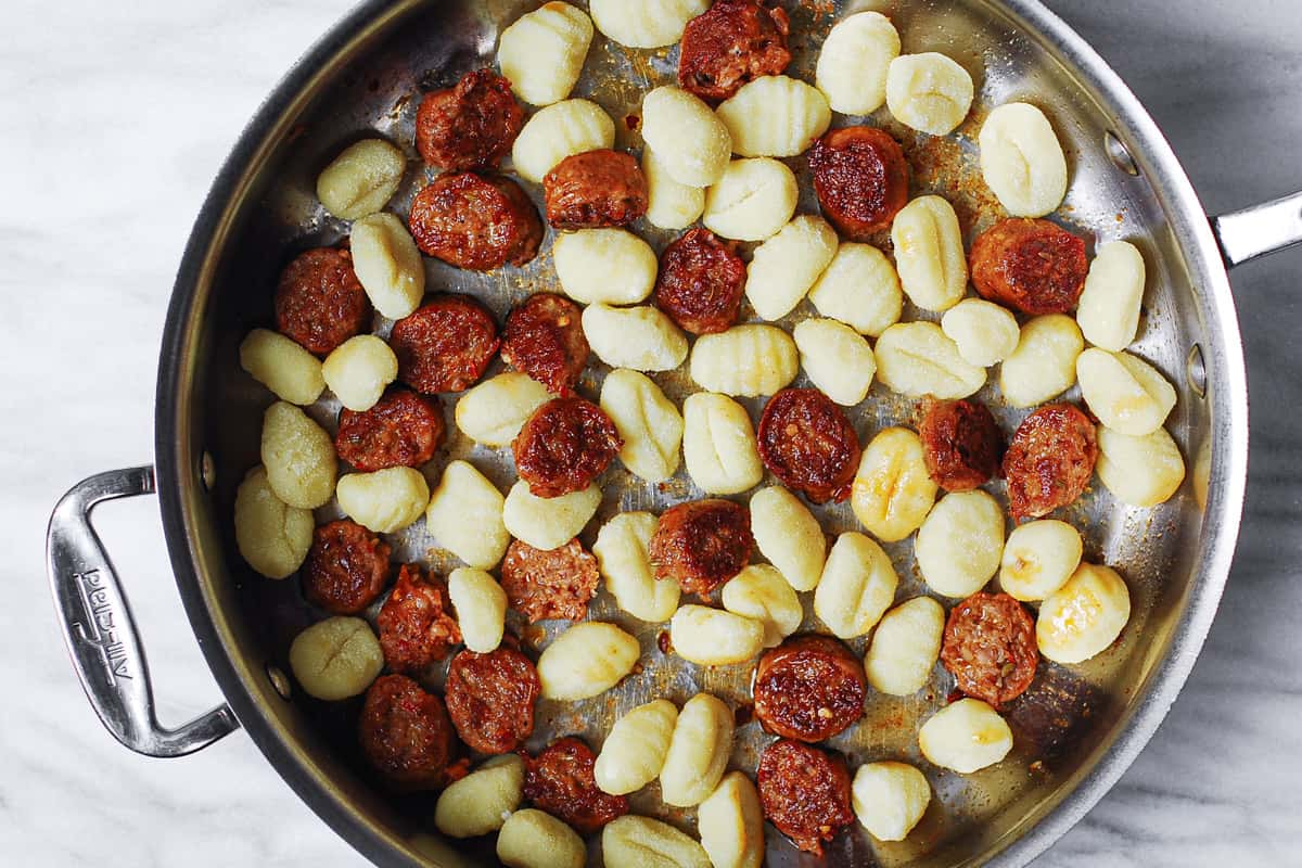 cooked sausage and potato gnocchi in a stainless steel pan