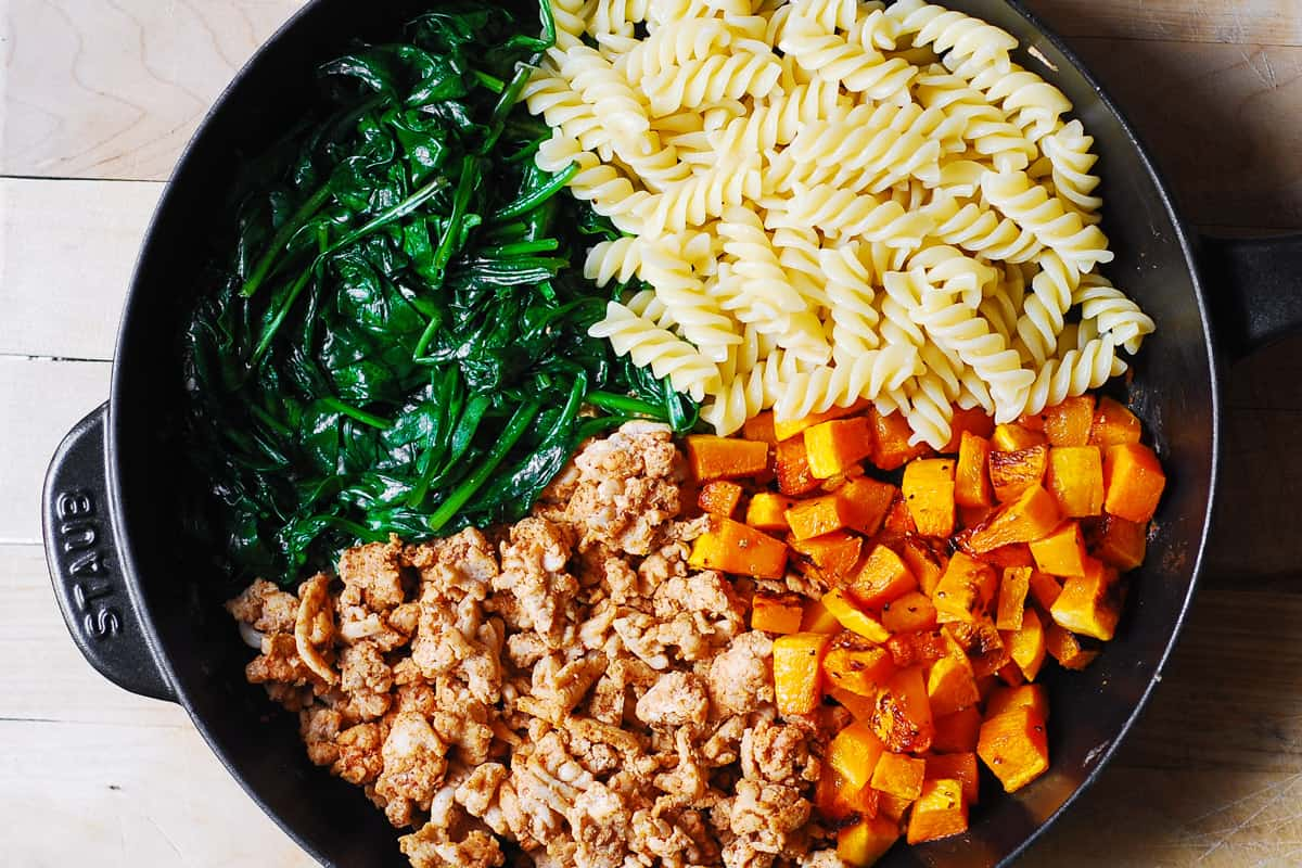 ingredients for ground turkey pasta in a cast iron skillet: cooked ground turkey, cooked pasta, roasted butternut squash, and cooked spinach